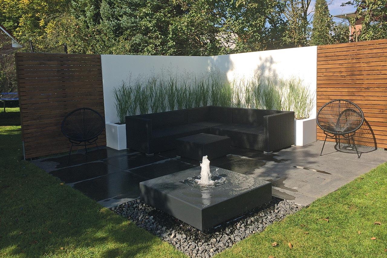 Moderner Gartenbrunnen auf der Terrasse zusammen mit Loungesesseln Loungeecke